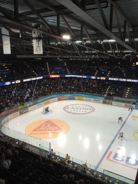 Patrick Fischer steht an Luganos Bande, direkt unter seiner «Retired Number 21» in Zug (Foto: eishockeyblog.ch)